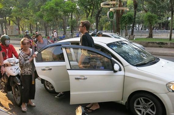 Du khách đi xe Uber tại trung tâm TP.HCM - Ảnh: TỰ TRUNG