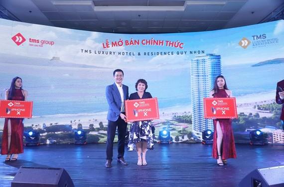 Đại diện chủ đầu tư Tập đoàn TMS tặng quà cho khách hàng đặt mua thành công căn hộ ngay tại sự kiện.