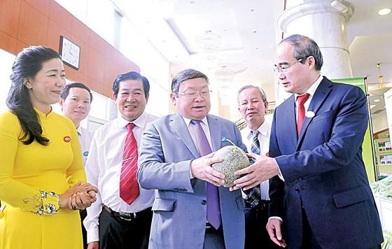 Bí thư Thành ủy TPHCM Nguyễn Thiện Nhân xem sản phẩm dưa lưới trồng tại TPHCM mang lại giá trị cao. Ảnh: CAO THĂNG