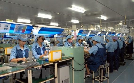 Công nhân sản xuất linh kiện điện tử tại Nhà máy Canon vốn đầu tư của Nhật Bản tại Khu Công nghiệp Phố Nối A. (Ảnh: Phạm Kiên/TTXVN)
