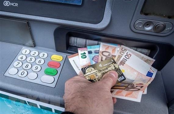 Khách hàng rút tiền đồng euro tại một máy rút tiền tự động ở Pháp. (Nguồn: AFP/TTXVN)