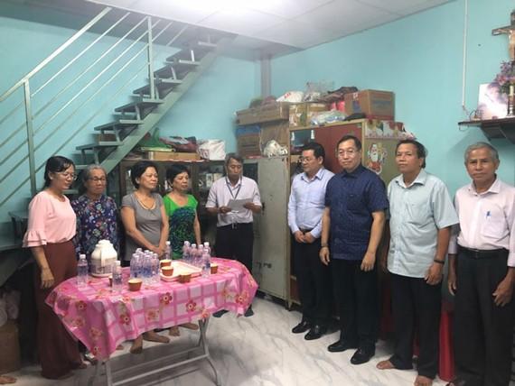 Ông Trần Hữu Trí (thứ 3 từ phải sang)- Bí thư, Chủ tịch HĐND Quận 12; ông Nguyễn Toàn Thắng (thứ 4 từ phải sang)- Giám đốc Sở TNMT TPHCM cùng đại diện các ban ngành trao nhà cho hộ bà Nài.