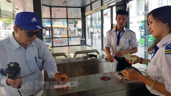 Khách sử dụng thẻ vé điện tử qua cổng kiểm soát để lên xe buýt nhanh BRT 01 Kim Mã-Yên Nghĩa. (Ảnh: Việt Hùng/Vietnam+)