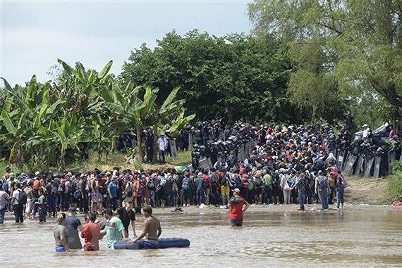 Người di cư băng qua sông Suchiate từ Ciudad Tecun Uman (Guatemala) để tới Ciudad Hidalgo (Mexico) trong hành trình đến Mỹ. Nguồn: TTXVN