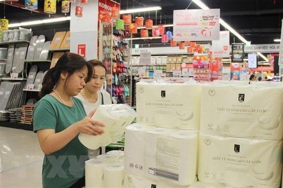 Người tiêu dùng mua sắm hàng tiêu dùng thiết yếu cho gia đình. (Ảnh: Mỹ Phương/TTXVN)