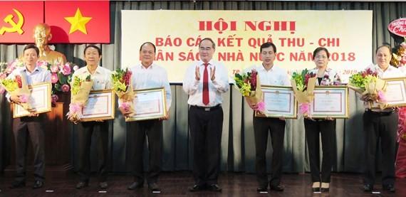Bí thư Thành ủy TPHCM Nguyễn Thiện Nhân trao tặng bằng khen của UBND TPHCM đối với các địa phương hoàn thành xuất sắc công tác thu nộp ngân sách Nhà nước trên địa bàn thành phố năm 2018. Ảnh: KIỀU PHONG