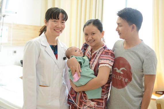 Bé Nguyễn Đặng Khôi Nguyên trong vòng tay của cha mẹ và bác sĩ Hồ Thị Xuân Nga khi xuất viện
