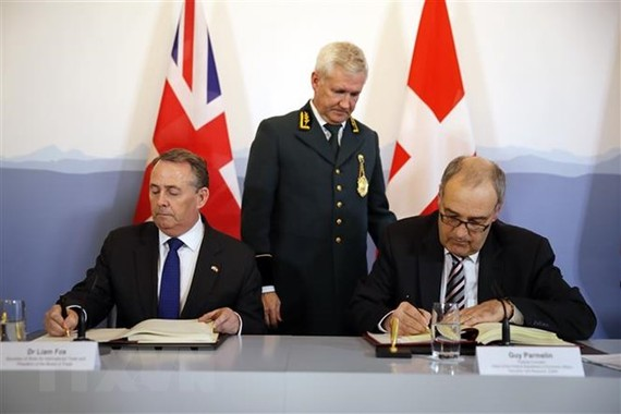 Bộ trưởng Thương mại Anh Liam Fox (trái) và Bộ trưởng Kinh tế Thụy Sĩ Guy Parmelin (phải) ký thỏa thuận duy trì hoạt động thương mại Anh - Thụy Sĩ tại Bern ngày 11/2/2019. (Ảnh: AFP/ TTXVN)
