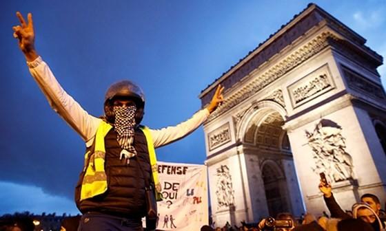 Người biểu tình áo vàng đứng trước Khải Hoàn Môn ở Paris ngày 22/12/2018. Ảnh: Reuters