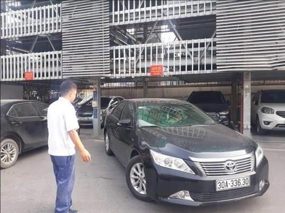 Nhân viên điểm trông giữ xe của Công Ty TNHH Một Thành Viên Khai Thác Điểm Đỗ Xe Hà Nội hướng dẫn xe ra vào điểm đỗ xe lắp ghép. (Ảnh: Tuyết Mai/TTXVN)