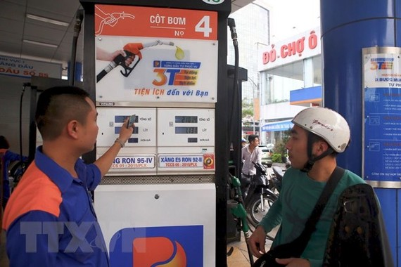 Khách đến mua xăng tại cửa hàng xăng dầu số 85, Nguyễn Văn Cừ, Gia Thuỵ, Long Biên, Hà Nội. (Ảnh: Minh Quyết/TTXVN)