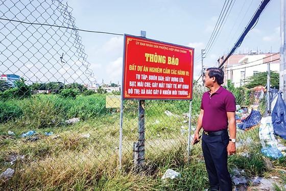 Ông Ngô Mạnh Hân bên cạnh mảnh đất của mình bị treo quyền lợi suốt 27 năm qua. Ảnh: M.TUẤN