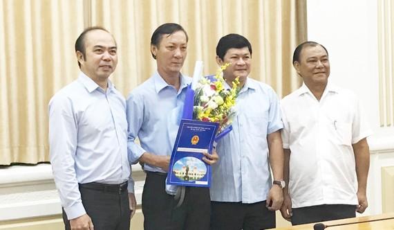 Phó Chủ tich UBND TPHCM Huỳnh Cách Mạng (thứ hai từ phải sang) và ông Hồ Văn Ngon (thứ ba từ phải sang) tại buổi trao quyết định. Ảnh: KIỀU PHONG