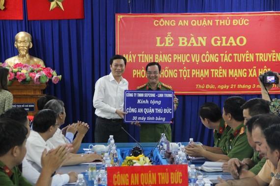 Đại tá Lê Anh Tuấn, Trưởng Công an quận Thủ Đức nhận máy tính bảng từ nhà tài trợ