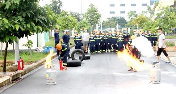 """Các """"lính cứu hỏa nhí"""" sử dụng bình chữa cháy dập tắt ngọn lửa phát ra từ bình gas"""