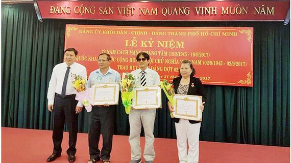 Đồng chí Trần Thế Lưu, Ủy viên Thường vụ, Trưởng Ban Nội chính Thành ủy TPHCM trao Huy hiệu 55, 45 và 40 năm tuổi đảng