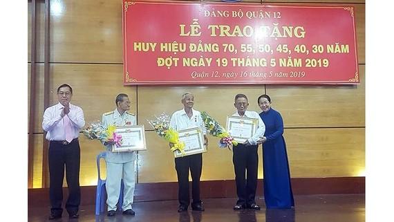Phó Bí thư Thành ủy Võ Thị Dung trao huy hiệu 70 năm tuổi Đảng cho các đảng viên