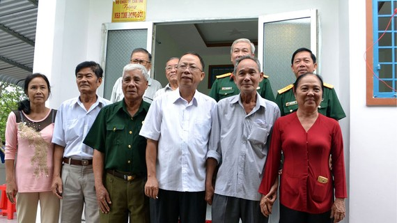 Các đại biểu chụp hình lưu niệm bên Nhà đồng đội vừa cất cho đồng chí Thượng tá Nguyễn Chiến Lang