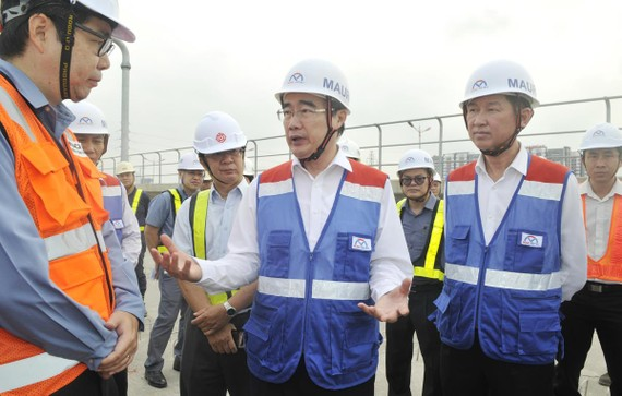Bí thư Thành ủy TPHCM Nguyễn Thiện Nhân trao đổi cùng đại diện nhà thầu tại buổi thị sát ở ga nổi Phước Long. Ảnh: CAO THĂNG