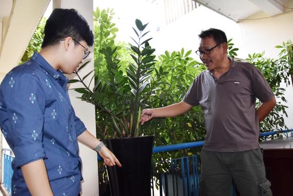 """Nhà sáng chế """"chân đất"""" Nguyễn Quang Ngọc (bìa phải) và cộng sự bên những cây lên xanh tốt với chậu trồng cây không cần tưới"""