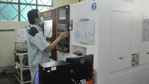 A worker operates CNC machine in Duy Tan Plastic Company. (Photo: SGGP)