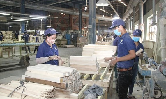 Workers process wood products for export at Tuong Van Company in Bac Tan Uyen District in Binh Duong Province. (Photo: SGGP)
