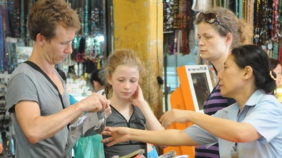 Foreign tourists buy goods at Ben Thanh Market. (Photo: SGGP)