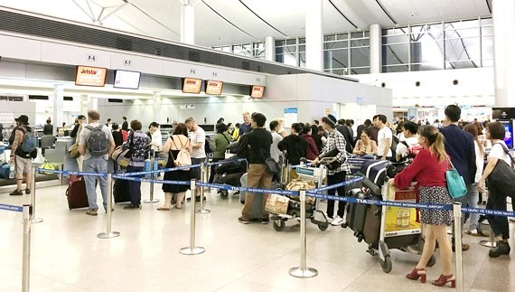 Passengers wait for luggage weighing at Tan Son Nhat International Airport. (Photo: SGGP)