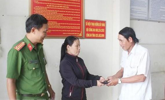Chị Lê Thị Hậu trao trả lại tài sản cho người đánh rơi tại Công an phường Thanh Bình, TP Biên Hòa. Ảnh: TTXVN