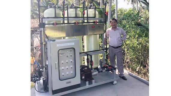 GS Nguyễn Văn Phước và mô hình xử lý nước lắp đặt tại ấp An Quy. Ảnh: IER