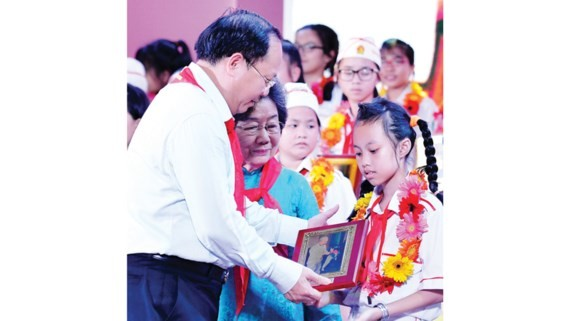 Standing Deputy Secretary of the Ho Chi Minh city Party Committee Tat Thanh Cang offered certificates of merit to outstanding children. (Photo: Sggp)