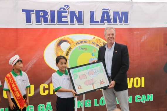 A student in Nong Son District presents a painting of wild elephants to U.S. Ambassador to Vietnam Ted Osius. (Photo: Sggp)