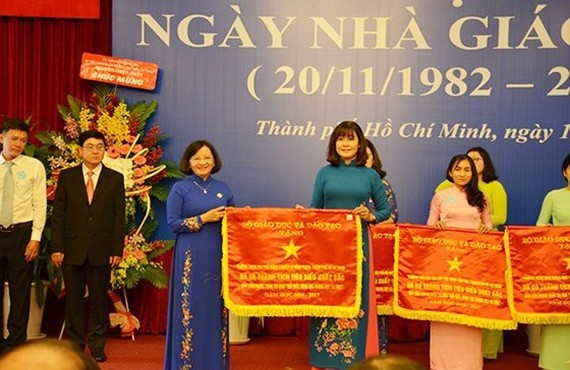 Head of the Department of Propaganda and Training of the HCMC Party Committee Than Thi Thu (in blue Ao Dai) presents the Government's emulation flag to the City's Department of Training and Education. (Photo: Sggp)