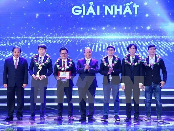 Prime Minister Nguyen Xuan Phuc (centre) and Minister of Information and Communications Truong Minh Tuan (first, left) present the first award in the field of IT (Photo: VNA)