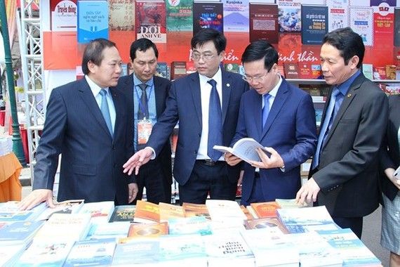 Politburo member and Head of the Party Central Committee's Commission for Communications and Education Vo Van Thuong (2nd, R) visits display booths at the 5th Vietnam Book Day. (Photo: Sggp)