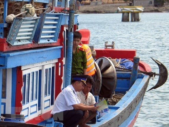 A law enforcement officer provides Ninh Thuan fishermen with fishing-related regulations (Source: VNA)