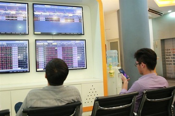 Two investors follow the stock index at the VNDirect Stock Exchange (Source: VNA)
