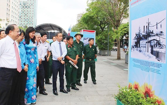 Deputy Secretaryof the Party Committee of Ho Chi Minh CityTat Thanh Cang (L) attends the exhibition in Nguyen Hue walking street. (Photo: Sggp)