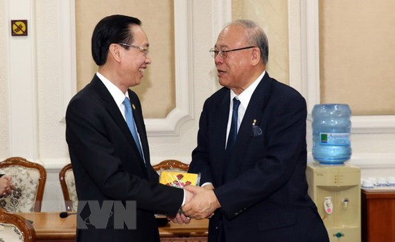 Standing Vice Chairman of the municipal People's Committee Le Thanh Liem (L) and Special Advisor of the Japan-Vietnam Parliamentary Friendship Alliance Tsutomu Takebe (Photo: VNA)