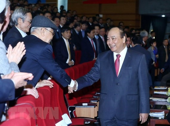 Prime Minister Nguyen Xuan Phuc (R) greets participants in the meeting of PetroVietnam in Hanoi on January 11 (Photo: VNA)