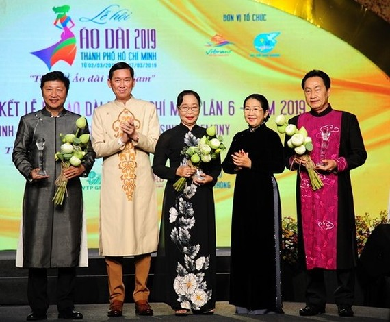 Vice Secretary of the Ho Chi Minh City Party Committee Vo Thi Dung (2nd, R) and Vice chairman of the municipal People's Committee Tran Vinh Tuyen (2nd, L) presents certificates of merit to people who have outstanding contribution to the festival. (Photo:
