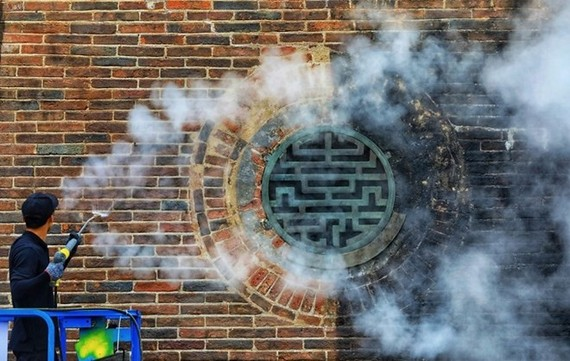 Many of the nearly 200-year-old gate's bricks (L) have regained their bright red color after 15 days. (Photo: vnexpress.net)