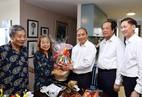 Prime Minister Nguyen Xuan Phuc (centre) presents a gift to former Chairwoman of the HCM City Journalists Association Nguyen Thi Hang Nga (second, left) on June 18 (Photo: VNA)