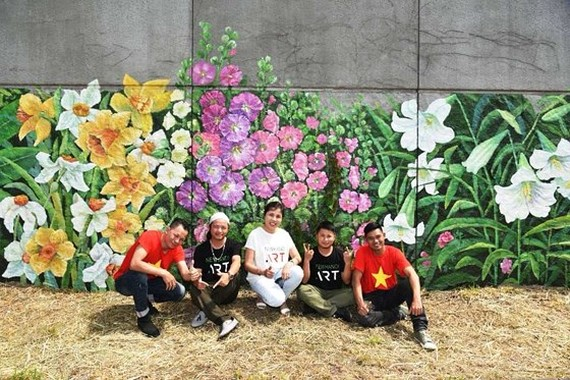 """The large picture titled """"France-Vietnam Spring"""" is painted by artist Nguyen Thu Thuy and her colleagues of the New Hanoi Art Company."""