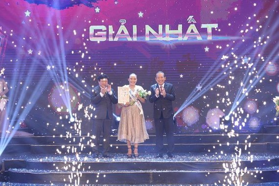 Deputy Prime Minister Truong Hoa Binh (R) presents first prize to Malaysian singer Rosario Ninih Chamini Bianis (Photo: VOV)