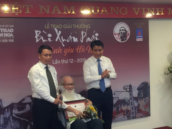 Assoc. Prof. Dr. Nguyen Thua receives the Grand Prize at the 12th Bui Xuan Phai Award-Love for Hanoi. (Photo: Sggp)