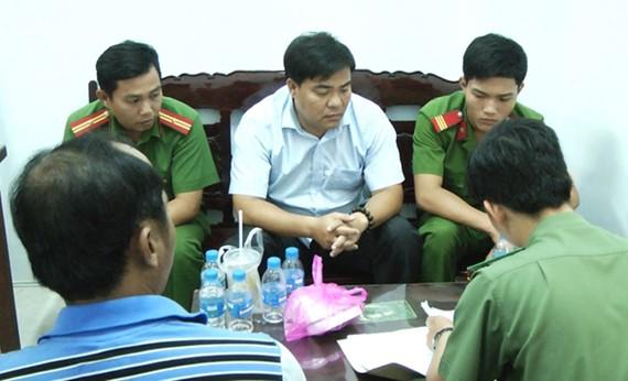 Công an Sóc Trăng tiến hành thủ tục bắt giữ ông Châu Hoài Phương (áo trắng). Ảnh: TRUNG HIẾU