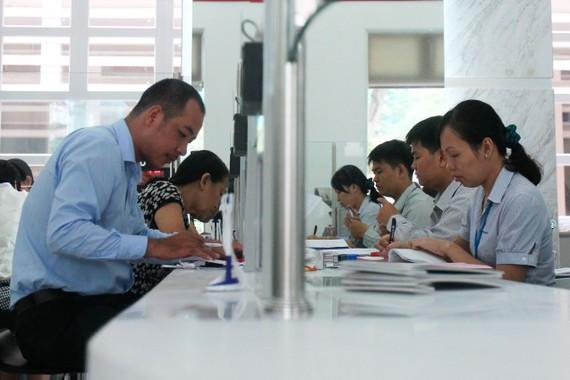 Cán bộ UBND quận 1 (TPHCM, bìa phải) giải quyết hồ sơ cho người dân