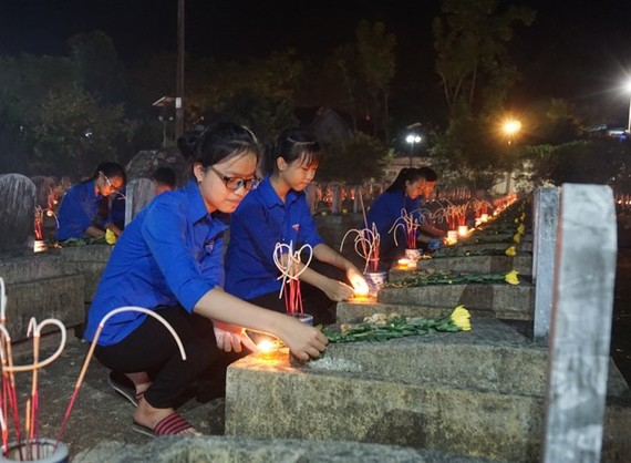 Students light up candles at the Vietnam-Laos martyr cemetery in the central province of Nghe An to remember more than 11,000 Vietnamese volunteer soldiers who laid down their lives in Laos during wartime. (Photo: dantri.vn)