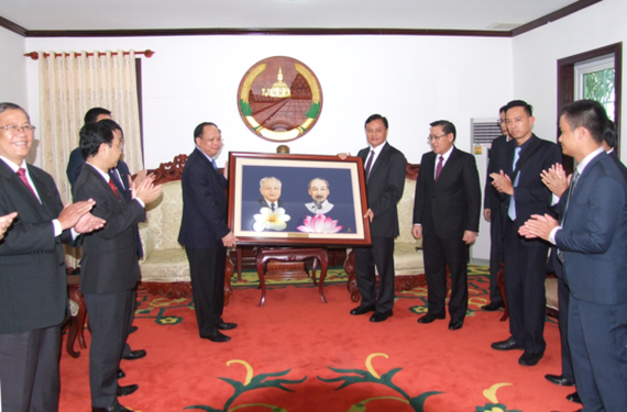 Deputy Standing Secretary of the Ho Chi Minh City Party Committee Tat Thanh Cang offers a portrait of Vietnamese President Ho Chi Minh and Lao President Cayson Phomvihan to Savannakhet province. (Photo:Ai Ch